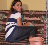Playful cutie in tight jeans showing her lovely feet on the sofa.